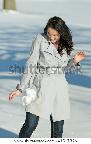 Young brunette woman in snowball fight - stock photo