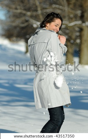 Young brunette woman in snowball fight - being hit - stock photo