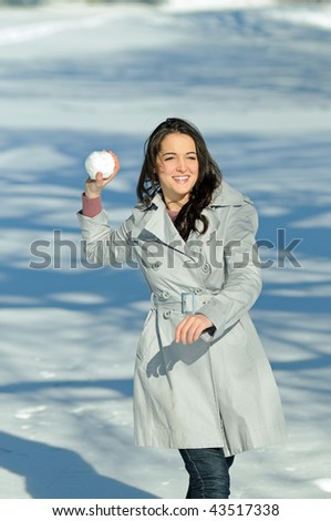 Young brunette woman in snowball fight - throwing - stock photo