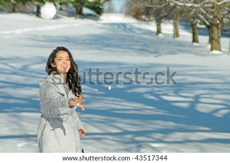 Young brunette woman in snowball fight - throwing