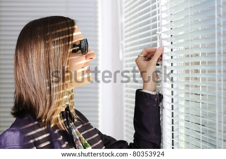 Young brunette woman in the sunlight looking through  jalousie on window