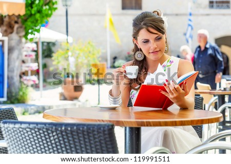 Young brunette woman is drinking coffee and reading book in a cafe - stock photo