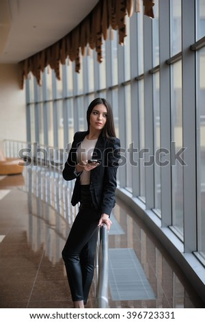 Young brunette woman is looking through the window on the planes and waiting to departure in the airport - stock photo