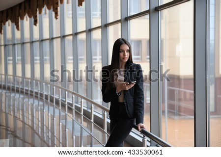 Young brunette woman is looking through the window on the planes and waiting to departure in the airport