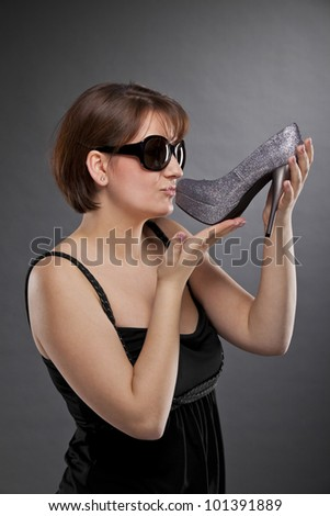young brunette woman kissing a shoe - stock photo