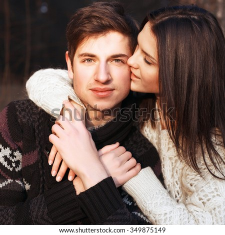 Young brunette woman kissing her man in love in winter cold weather  - stock photo