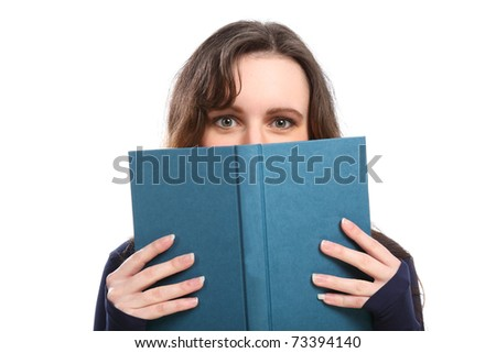 Young brunette woman looking up from behind a book she is reading. - stock photo