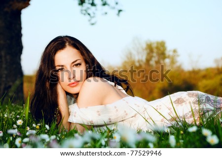 young brunette woman lying in grass, summer day