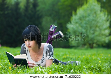 Brunette woman lying on grass and reading a poetry in spring park