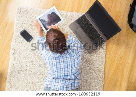 Young brunette woman lying on the floor using her tablet and notebook in the living room - stock photo