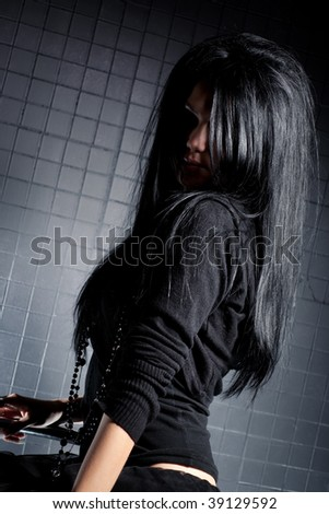 Young brunette woman. On dark wall background. - stock photo