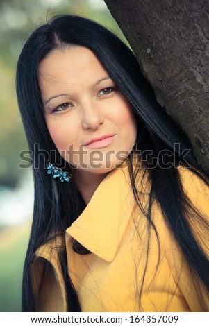 Young brunette woman outdoor.  Portrait of beautiful elegant woman  in autumn park looking away
