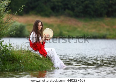 Young brunette woman playing tambourine at a lake