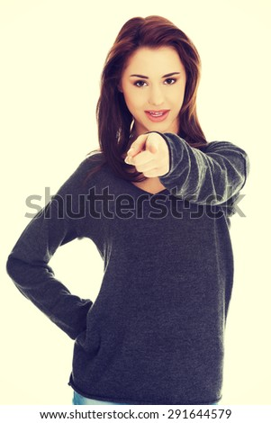 Young brunette woman pointing by a finger - stock photo