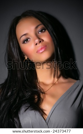 Young brunette woman portrait. On dark wall background. - stock photo