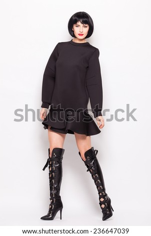young brunette woman posing in modern black clothes with high heel long boots - stock photo