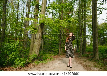 Young brunette woman posing in the green dark coniferous forest