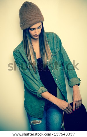 Young brunette woman posing with a skateboard - stock photo