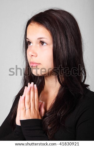 Young brunette woman praying and looking up - stock photo