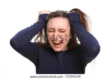 Young brunette woman pulling at her hair, eyes closed with angry and frustrated expression on her face. - stock photo
