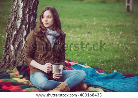 Young brunette woman resting under a tree during trip. Caucasian backpacker woman holding a mug outdoor. - stock photo