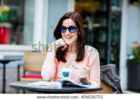 Young brunette woman sitting at a coffeeshop relaxing with her Cappuccino / Coffee while sitting outdoors - stock photo
