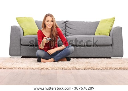 Young brunette woman sitting in front of a gray sofa and watching TV isolated on white background - stock photo