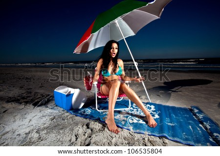 Young Brunette Woman sitting on beach chair under umbrella at the beach