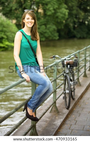 young brunette woman sitting on railing next to river