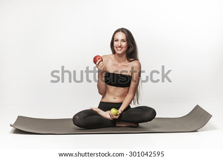 Young brunette woman sitting on yoga mat. Woman holding apple. Healthy lifestyle photo of Caucasian fitness model isolated on white. Healthy diet concept. - stock photo