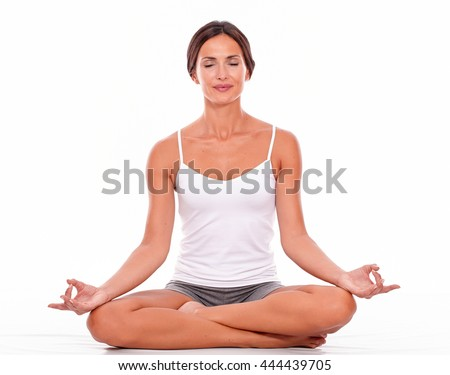 Young brunette woman sitting with her legs crossed while meditating with closed eyes and wearing a white tank top and gray shorts isolated - stock photo