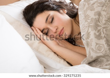 Young brunette woman sleeping in bed covered with a beige flowered quilt - stock photo