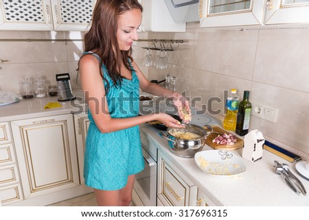 Young Brunette Woman Sprinkling Grated Cheese on Pasta in Pot While Preparing Home Cooked Meal for Dinner in Kitchen - stock photo
