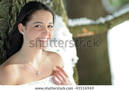 Young brunette woman standing outside next to snowy tree - smiling - stock photo