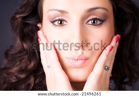 Young brunette woman tender portrait. On dark background.