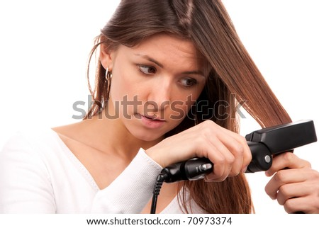Young brunette woman using hair straighteners black flat iron to make new stylish hairstyle isolated on a white background