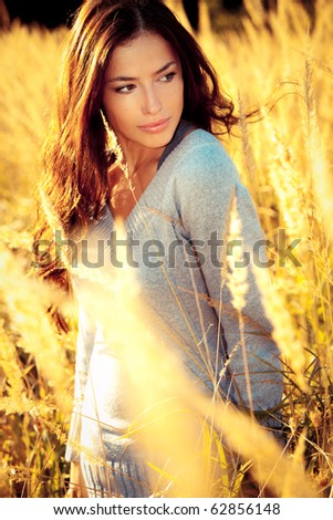 young brunette woman  walking  through sunny yellow autumn field - stock photo