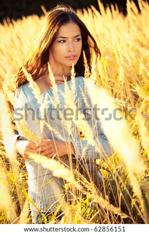 young brunette woman  walking  through sunny yellow autumn field