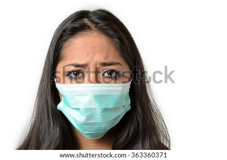 Young brunette woman wearing a disposable face mask to combat air pollution or safeguard against an epidemic or illness