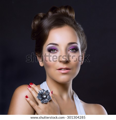 young brunette woman with beautiful makeup and hair, wearing a silver ring - stock photo