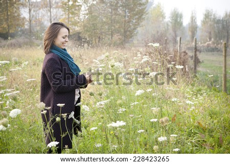 young brunette woman with coat picking wildflowers in the countryside with sunlight and trees on the background - stock photo