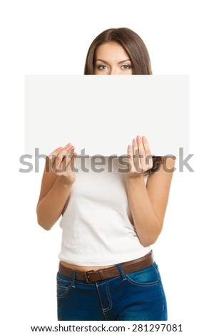 Young brunette woman with face covering by signboard or paper card, with empty blank copyspace area for text or slogan. Caucasian model looking over small poster. - stock photo