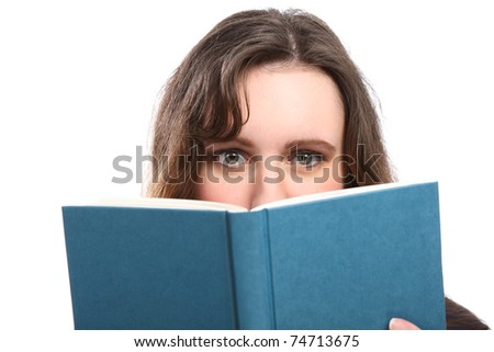 Young brunette woman with green eyes looking up from behind a book she is reading. - stock photo