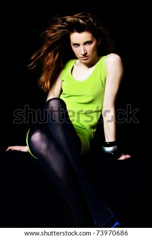 young brunette woman with long flying hair in green dress, studio shot