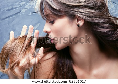 young brunette woman with nourished long  hair, studio shot, profile, - stock photo