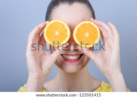 Young brunette woman with oranges in her hands