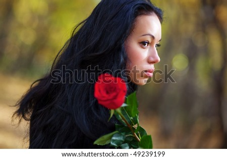 Young brunette woman with red rose portrait. - stock photo