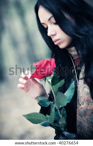Young brunette woman with red rose portrait. Soft colors. - stock photo