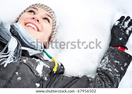 Young brunette woman with winter outfit lying on snow making snow angel. - stock photo