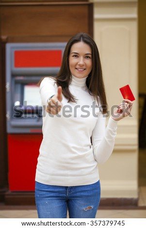 Young brunette woman withdrawing money from credit card at ATM  - stock photo